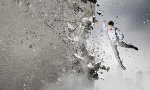 Emotional businessman breaking stone wall with karate punch